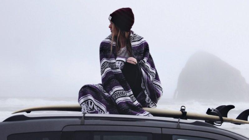 Surfeuse sur planche sur une voiture